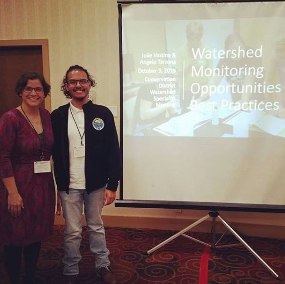 Angelo Tarzona and Julie Vastine standing in front of a presentation