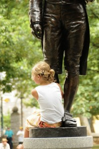 A young bluegrass fan perches on Benjamin Rush's foot.