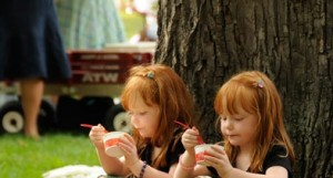 Twins little girls eat ice cream at festival