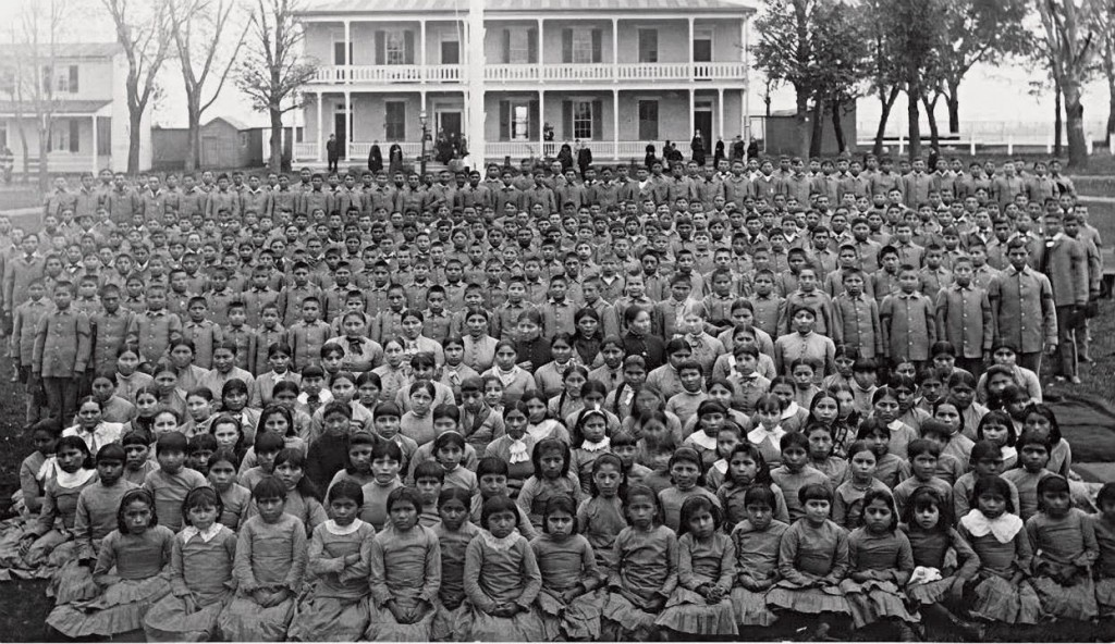 black and white photo of hundreds of school students sitting in rows in front a school building