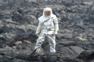 Sasha Belousov in lava suit preparing to collect sample