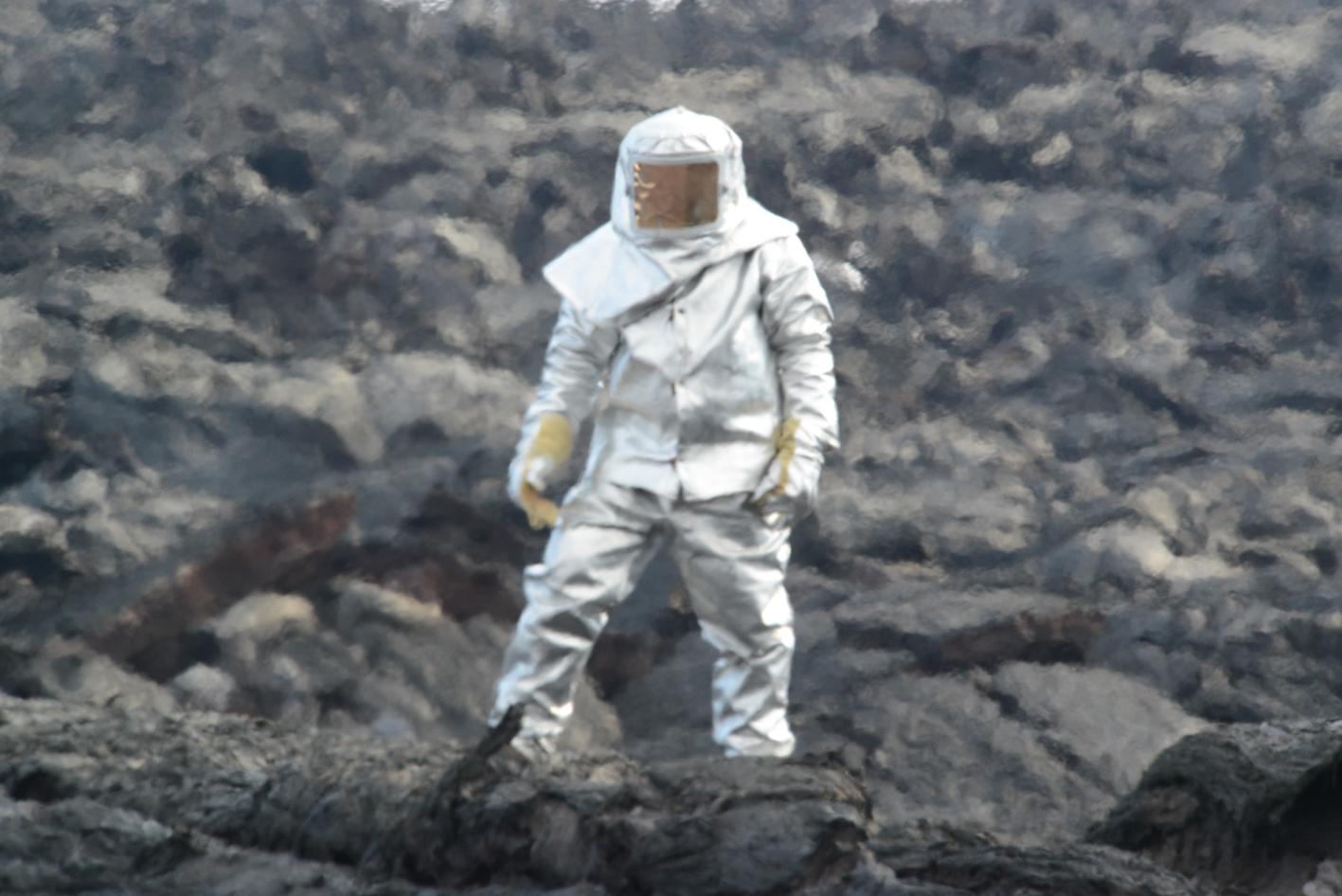 Sasha Belousov in lava suit preparing to collect sample