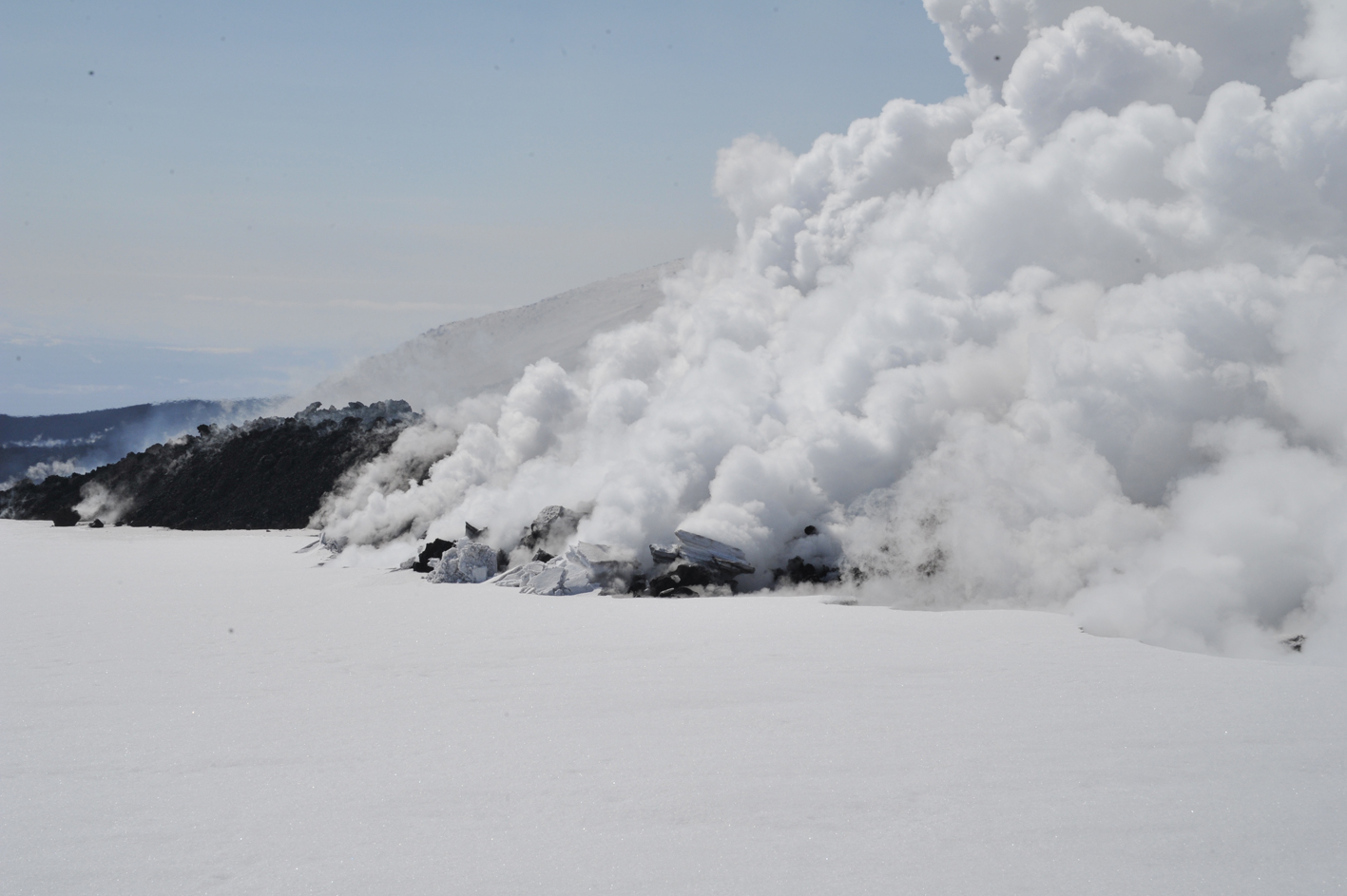 Steaming from 'snow dome', where lava is pushing up blocks of snow.