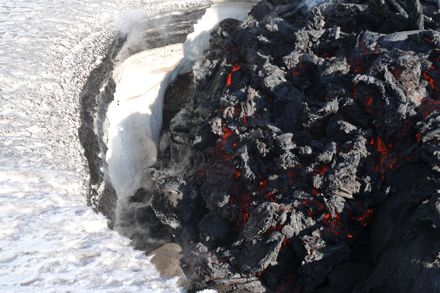 Front of advancing lava flow moving against snow bank.