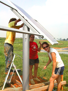 Student workers install solar panels.