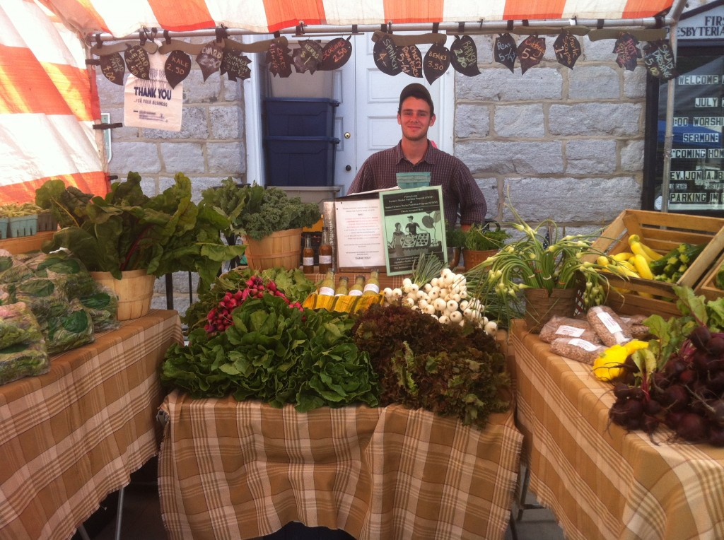 Sam Bogan, student farmer, at Dickinson College Farm's market stand.