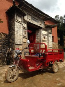 A three wheeled electric farm cart outside a mountain temple