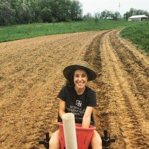 Sara riding on a tractor holding a bucket