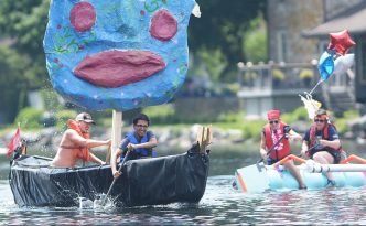 Two people rowing a boat with a giant blue face