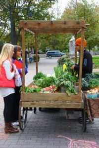 Evan as a student farmer managing the farm stand. He is selling farm produce, mostly greens, to two people on Britton Plaza