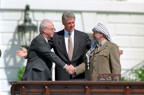 PLO President Yasser Arafat and Israeli PM Yitzhak Rabin shaking hands with US president Bill Clinton between them, after the signing of the Oslo Accords