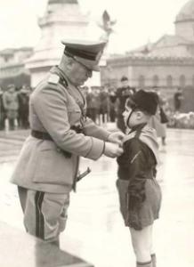 Mussolini con un Balilla (https://it.wikipedia.org/wiki/Opera_nazionale_balilla#/media/File:Mussolini_con_un_%22Balilla%22.png)