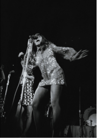Tina Turner on stage, singing into a microphone in its stand, one arm out to her side, the other lifted but partially obscured, and wearing a long-sleeved, short sequin shift