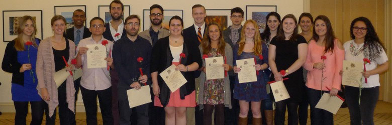 New member of Sigma Delta Pi stand holding their certificates, carnations, red candles and pins after the ceremony.