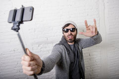 young-hipster-trendy-blogger-man-holding-stick-recording-selfie-video-vlog-concept-attractive-casual-clothes-beanie-style-68396568